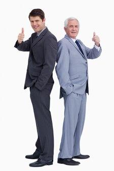 Homens de negócios de pé de costas dando polegares para cima