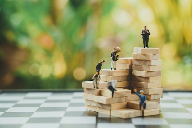 Homens de negócios diminutos dos povos que estão a análise ou o investimento de investimento.