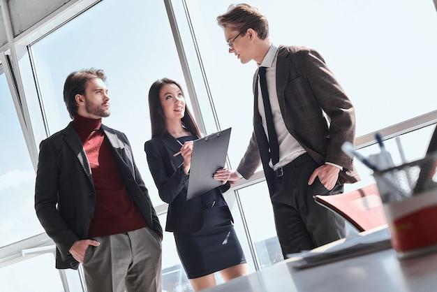 Homens de negócios e mulher de negócios trabalhando juntos em pé, homens conversando com uma mulher, fazendo anotações, segurando o suporte de papel, sorrindo e concentrados na conversa