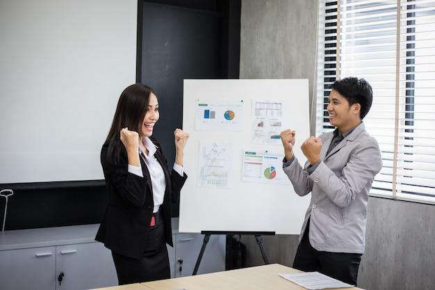 Homens de negócios e mulheres de negócios asiáticos sucesso e conceito de vencimento - equipe feliz com as mãos levantadas, comemorando a descoberta e as realizações