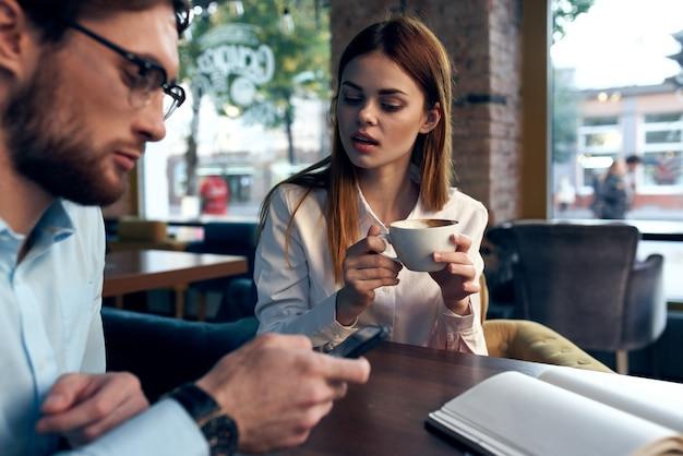 Homens de negócios e mulheres sentados em um café, uma xícara de café, comunicação de lazer