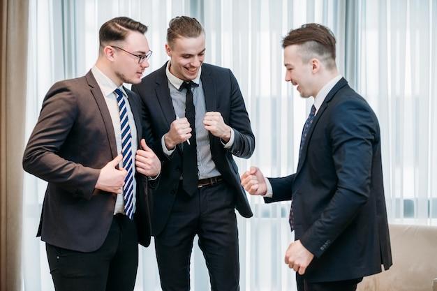 Homens de negócios felizes e sorridentes fazendo uma dança de comemoração no escritório