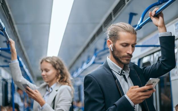Homens de negócios jovens viajando no metrô.