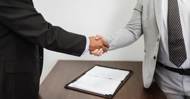Homens de negócios latinos fazendo aperto de mão após acordo fechado na mesa no escritório.