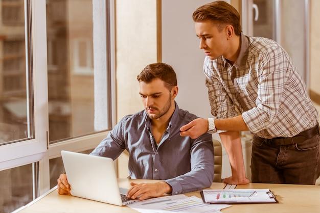 Homens de negócios na roupa usando o portátil ao trabalhar no escritório.