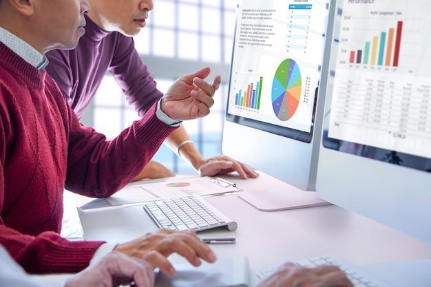 Homens de negócios olhando para telas de computador modernas, analisando o desempenho dos negócios e o retorno do investimento, roi, com gráficos coloridos.