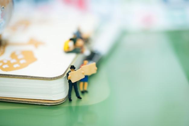 Homens de negócios pequenos que leem o jornal e que estão na frente do caderno.