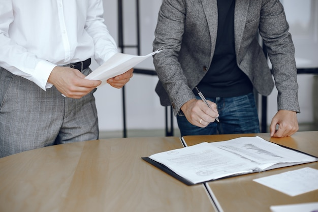 Homens de negócios sentados à mesa dos advogados. pessoas assinando documentos importantes.