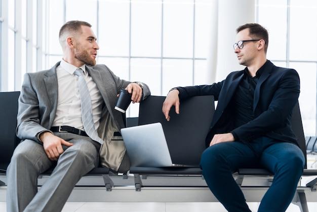 Homens de negócios trabalhando juntos no laptop no saguão do aeroporto