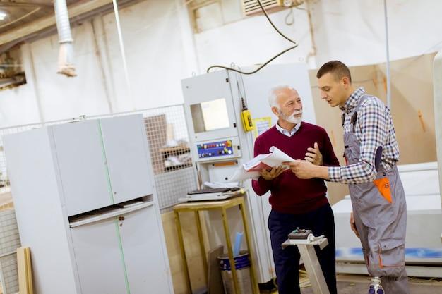 Homens de pé e discutir na fábrica de móveis, um deles é uma pessoa com deficiência