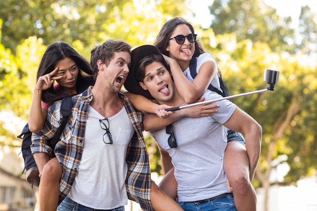 Homens de quadril dando piggy volta para suas namoradas e tomando selfie na rua