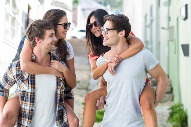 Homens de quadril dando piggy volta para suas namoradas na rua