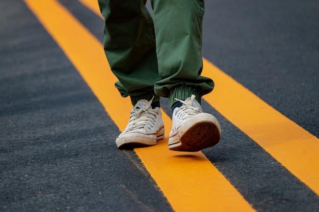 Homens de tênis andando nas ruas com linhas amarelas.