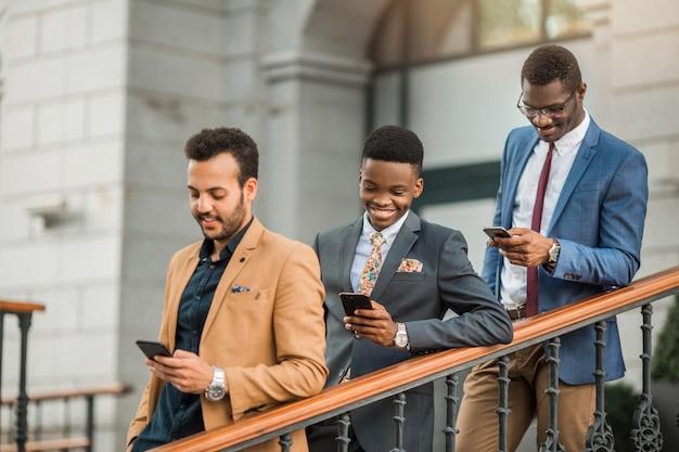 Homens de terno com telefones nas mãos