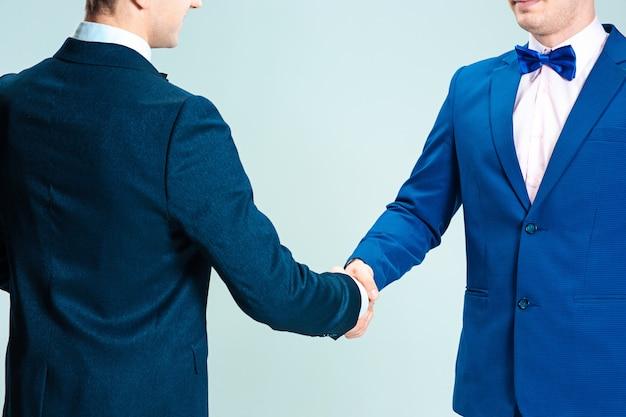 Homens de terno elegante, apertando as mãos, o conceito de acordos