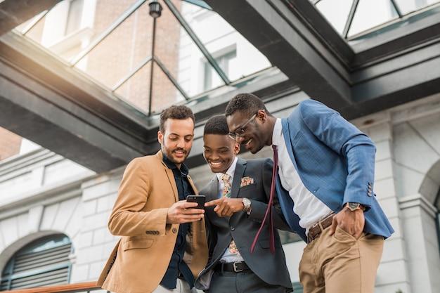 Homens de terno estão olhando para o smartphone