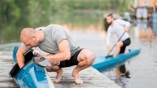 Homens de tiro completo com canoas ao ar livre