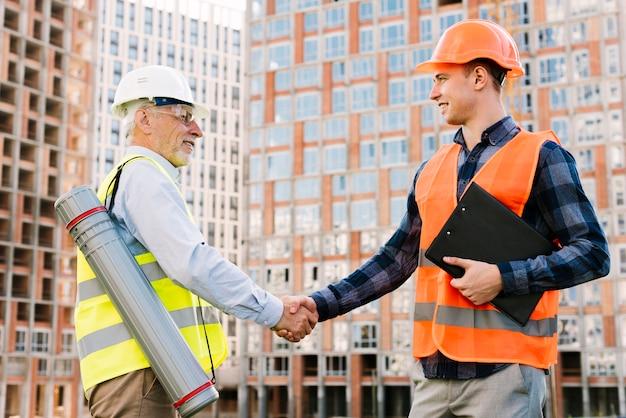 Homens de vista lateral com coletes de segurança apertando as mãos