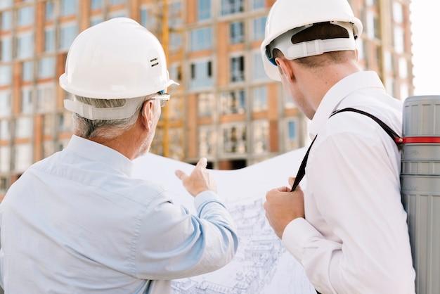 Homens de vista traseira, olhando para o projeto de construção