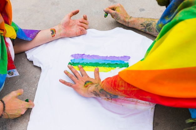 Homens desenhando arco-íris em t-shirt