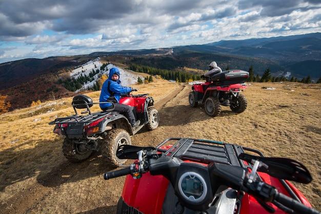 Homens dirigindo quad motos na frente no topo da montanha