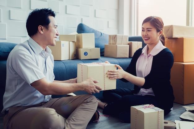 Homens do conceito das pme e trabalhador das mulheres que embalam a caixa do pacote no escritório