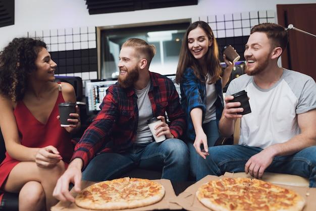 Homens e duas mulheres no estúdio de gravação estão comendo pizza.