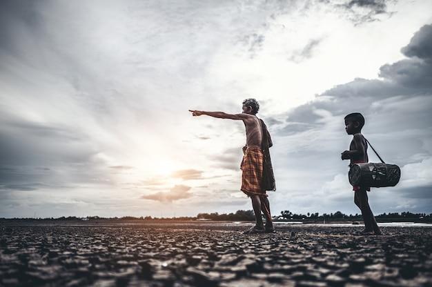 Homens e menino idosos encontram peixes em solo seco, aquecimento global