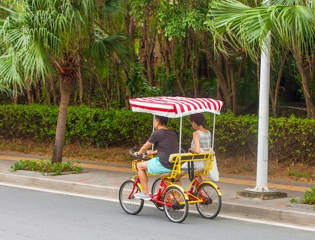 Homens e mulheres andam de bicicleta de quatro rodas.