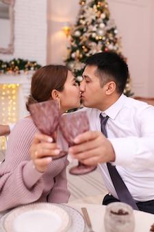 Homens e mulheres asiáticos celebram o natal bebendo vinho na mesa de jantar perto da árvore e da lareira