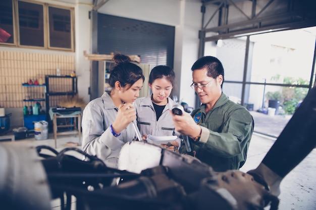 Homens e mulheres asiáticos engenheiros e técnicos estão reparando aeronaves