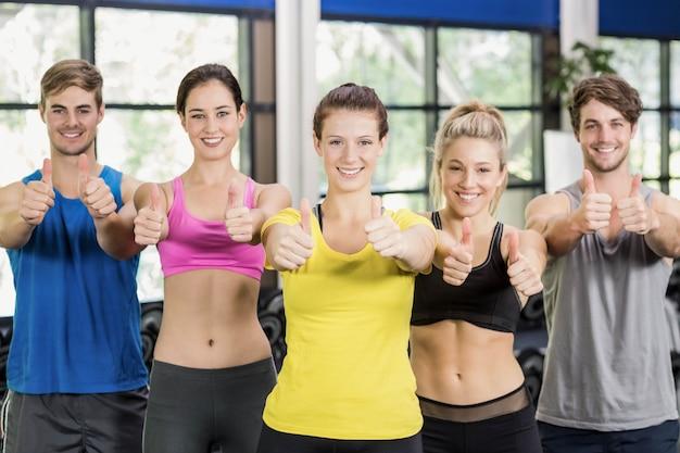 Homens e mulheres atléticos posando com polegares para cima no ginásio