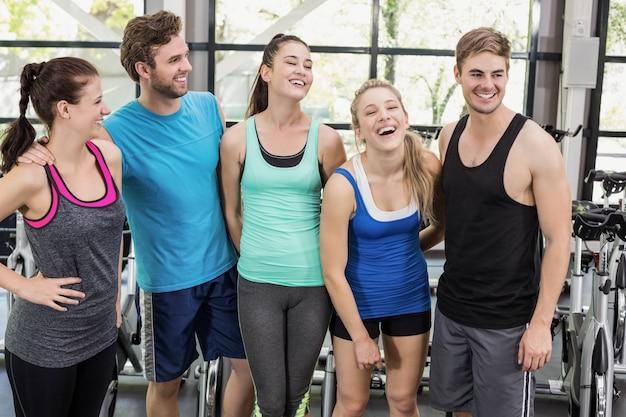 Homens e mulheres atléticos posando juntos no ginásio crossfit