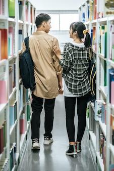 Homens e mulheres carregando uma mochila e procurando livros na biblioteca.