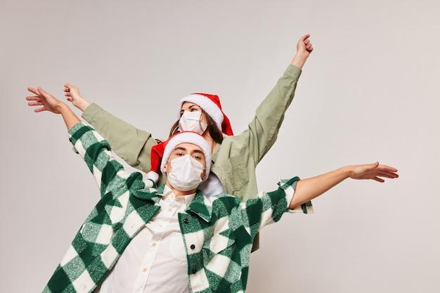 Homens e mulheres com chapéus de ano novo acesos em uma luz gesticulam com as mãos.