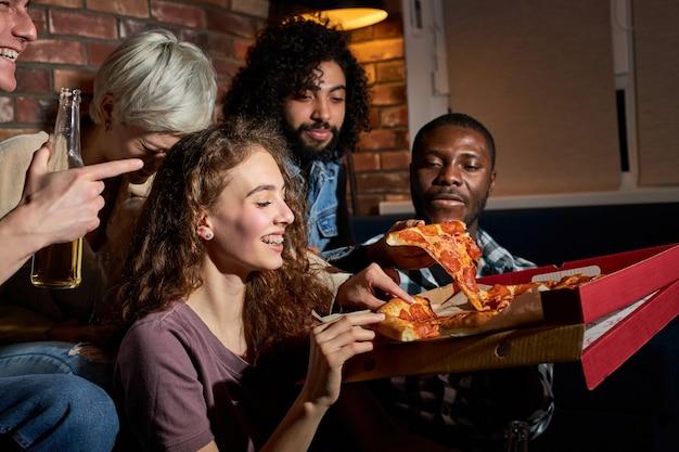 Homens e mulheres comendo pizza e assistindo tv. festa em casa. conceito de fast food. americanos passando tempo livre juntos à noite