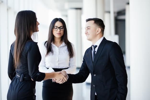 Homens e mulheres de negócios apertando as mãos, terminando uma reunião