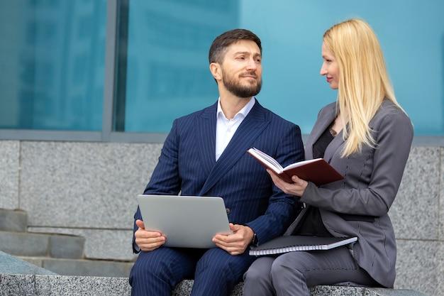 Homens e mulheres de negócios bem-sucedidos com documentos e laptop nas mãos discutem projetos de negócios