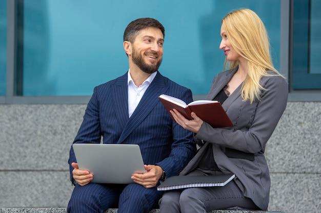 Homens e mulheres de negócios bem-sucedidos estão sentados na escada de um prédio comercial com documentos e um laptop nas mãos, discutindo projetos de negócios