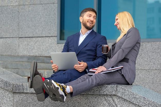 Homens e mulheres de negócios bem-sucedidos sentam-se na escada de um prédio comercial com documentos e um laptop