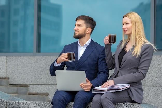 Homens e mulheres de negócios bem-sucedidos sentam-se nas escadas de um prédio comercial com documentos e um laptop nas mãos, bebem café e observam a beleza da cidade