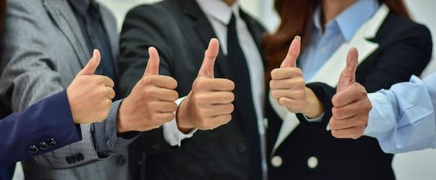Homens e mulheres de negócios estão mostrando polegares para cima conceitos que concordam.