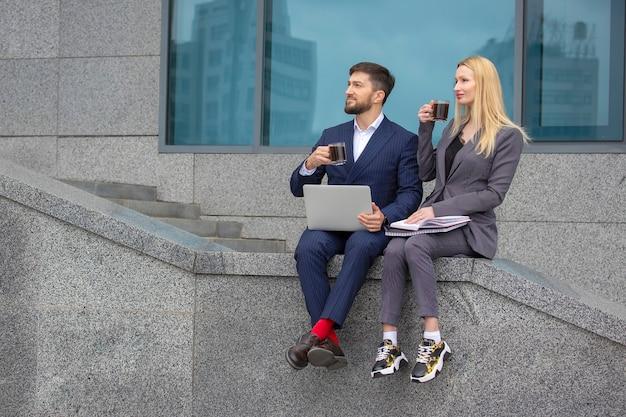 Homens e mulheres de negócios sentados na escada de um prédio comercial com documentos e um laptop nas mãos, bebendo café e discutindo o plano de trabalho do negócio
