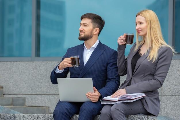 Homens e mulheres de negócios sentados na escada de um prédio comercial com documentos