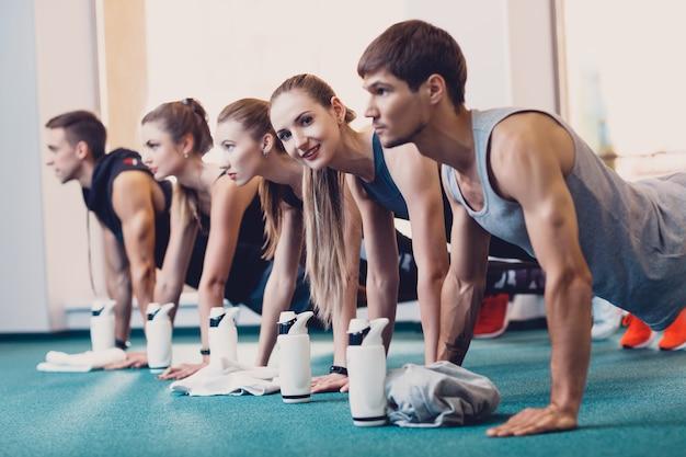 Homens e mulheres do grupo realizam um exercício físico.