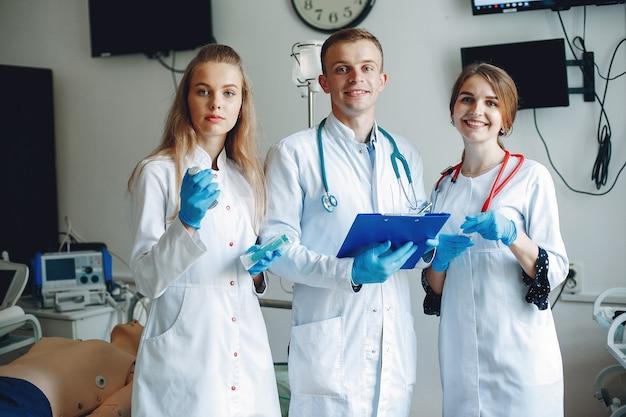 Homens e mulheres em aventais de hospital têm equipamentos médicos nas mãos