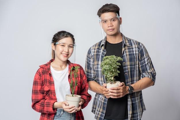 Homens e mulheres em pé e segurando vasos de plantas em casa