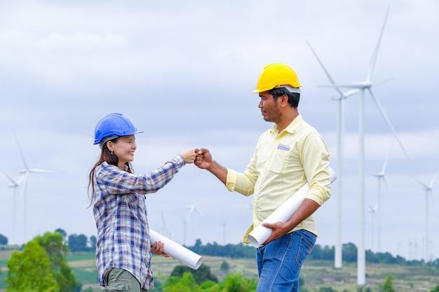 Homens e mulheres engenheiros industriais planejam desenvolver a energia eólica.