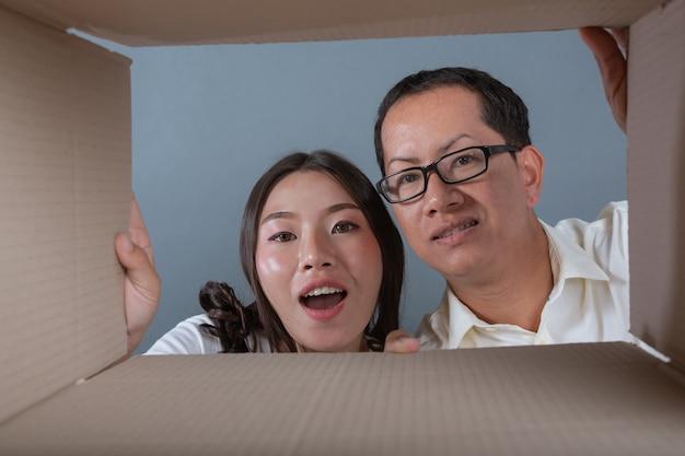 Homens e mulheres estão ajudando a arrumar as caixas.