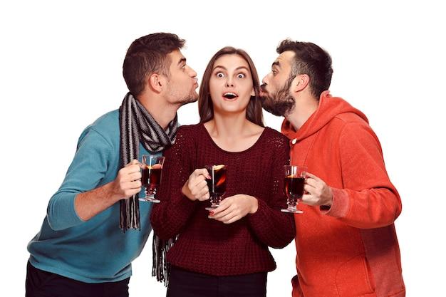 Homens e mulheres europeus sorridentes durante a sessão de fotos da festa. caras posando de amigos no estúdio fest com um copo de vinho com vinho quente quente em primeiro plano.
